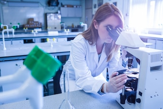 Scientist working with a microscope in laboratory