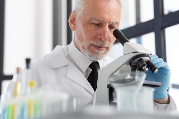 현미경을 사용하는 과학자를 닫습니다.