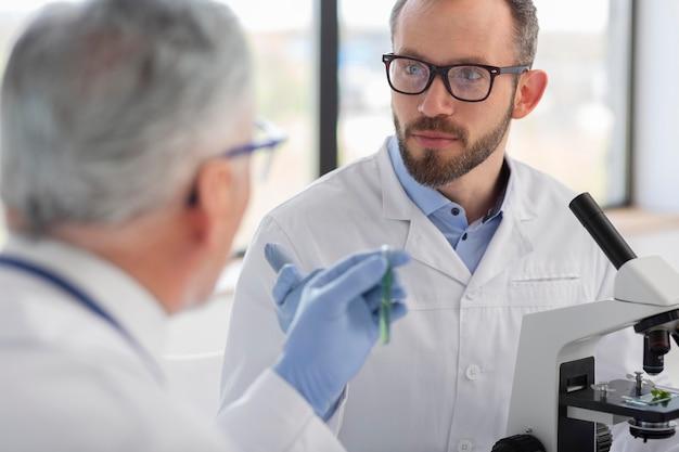 Scienziato che lavora con il microscopio da vicino