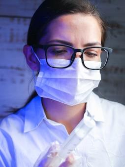 科学者は有害な化学物質を扱います。実験室の労働者は、生物学的に危険な液体、危険な作業、化学を調べます。慎重な作業。