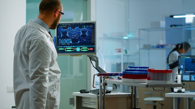 Scientist worried about virus evolution analysing dna scan image standing in equipped laboratory typing at computer. stuff examining vaccine development using high tech researching treatment