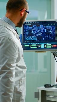 과학자는 컴퓨터에서 타이핑을 하는 장비를 갖춘 실험실에 서 있는 dna 스캔 이미지를 분석하는 바이러스 진화에 대해 걱정했습니다. 첨단 연구 치료제를 활용한 백신 개발을 검토하는 것들
