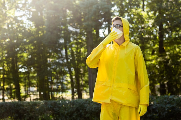 Scientist in yellow protective suit, glasses and respirator.