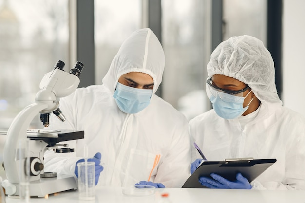 Ppe 슈트와 안면 마스크를 착용 한 과학자와 미생물학자는 실험실에서 시험관과 현미경을 들고 코로나 바이러스 감염에 대한 치료법이나 백신을 찾습니다. covid-19, 실험실 및 백신 개념.