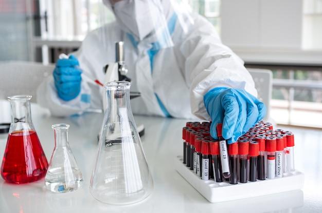 Ученые и микробиологи в костюме для индивидуальной защиты и в маске для лица держат пробирку с кровью, собранной у пациентов19, чтобы создать вакцину от коронавируса.