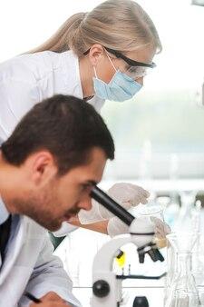 직장에서 과학자입니다. 그의 여성 동료가 백그라운드에서 실험을 하는 동안 현미경을 사용하는 남성 과학자의 측면