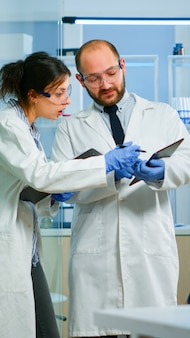 Scientists coworkers using digital tablet working in medical research laboratory, analysing biochemicals samples, talking. scientific lab for medicine, microbiology development with advanced equipment