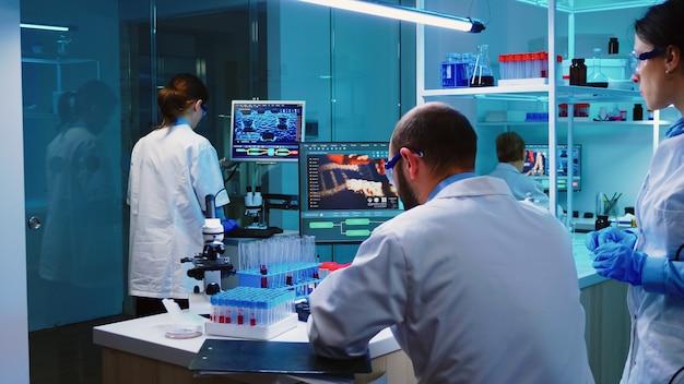 Ученые-коллеги, работающие в химической лаборатории, оснащенной современным оборудованием, в ночное время, анализируя результаты испытаний