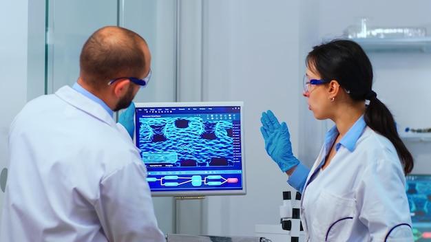Ученые-сотрудники работают в современной химической лаборатории. многонациональный персонал, изучающий эволюцию вакцины с использованием высоких технологий и технологий, исследует лечение против вируса covid19