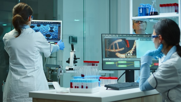 Ученые-сотрудники работают в современной химической лаборатории сверхурочно. врачи изучают эволюцию вакцины с использованием высоких технологий и технологий, исследуют лечение против вируса covid19
