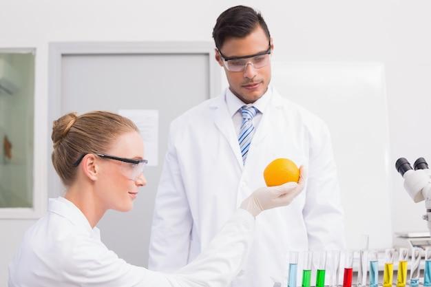 オレンジ色の実験をしている科学者
