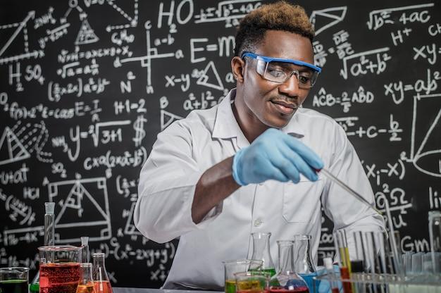 Ученые бросают химические вещества в стакан в лаборатории
