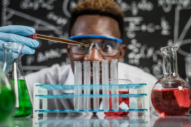 Ученые бросают оранжевые химикаты в стакан в лаборатории