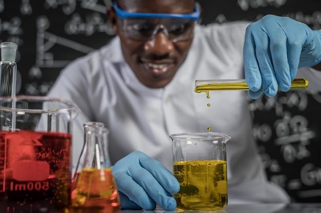 Ученые сбрасывают в стакан желтые химикаты в лаборатории