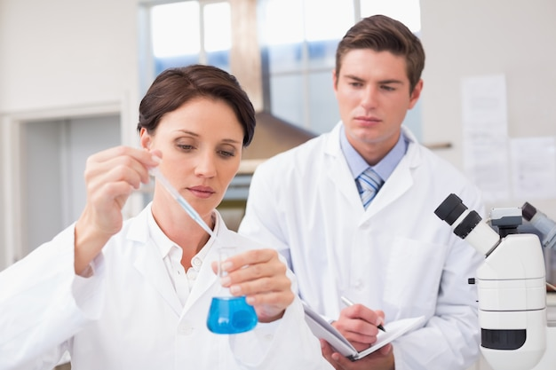 Scientists examining attentively pipette with blue fluid