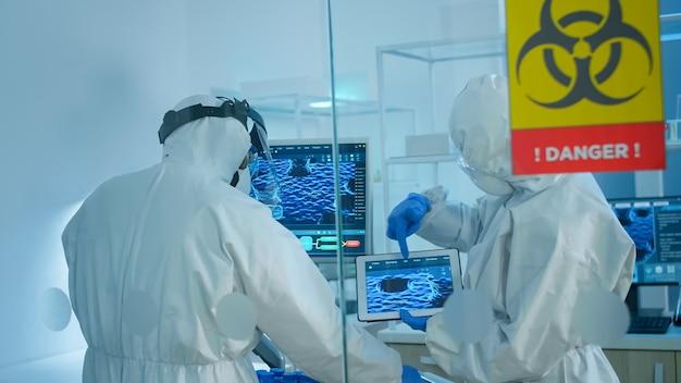 실험실의 위험 지역에서 작업하는 유리 벽 뒤에 서있는 작업복을 입은 과학자들