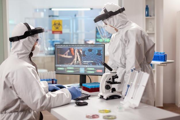 바이러스에 감염된 dna 샘플을 분석하는 보호 복의 과학자