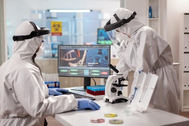 바이러스에 감염된 dna 샘플을 분석하는 보호복을 입은 과학자