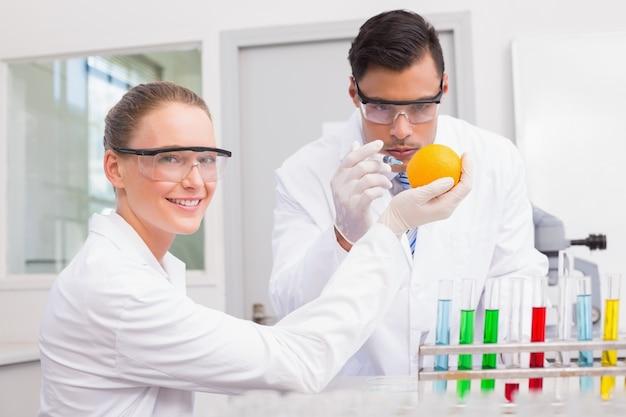 オレンジを注入する科学者