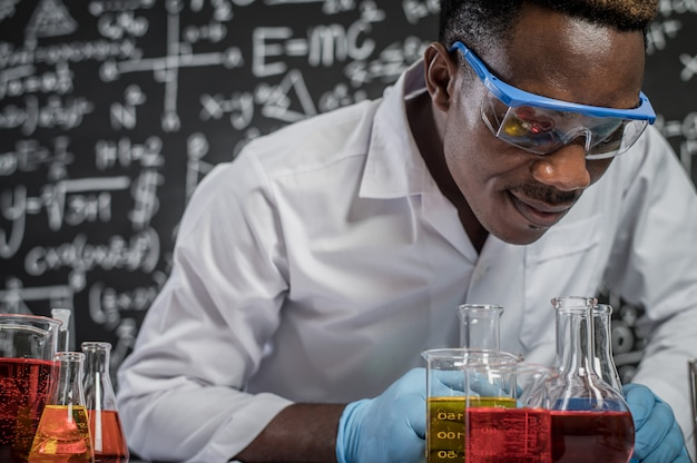 Ученые смотрят на химикаты в стекле в лаборатории