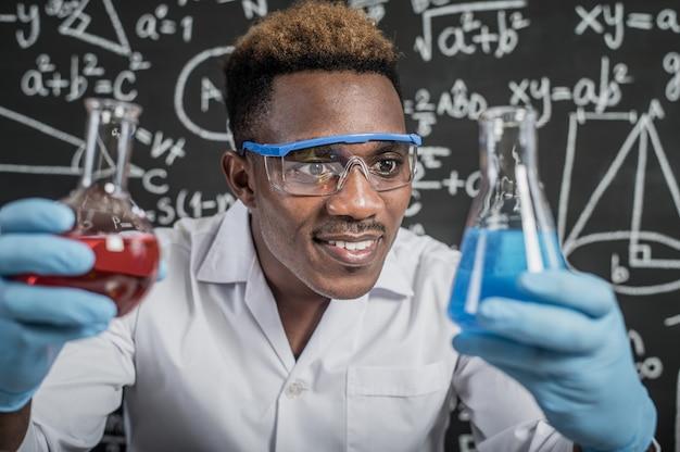 Ученые смотрят на небесно-голубые химические вещества в стакане в лаборатории