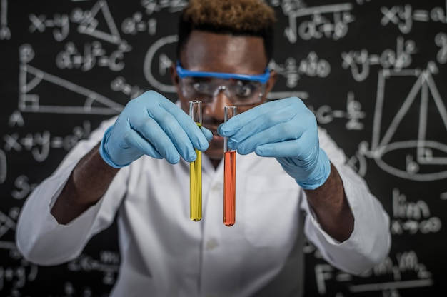 Scientists look at the orange and yellow chemicals in glass at the laboratory
