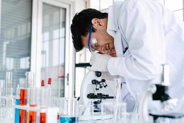Ученые смотрят в микроскоп, проверяя эксперимент, проводя медицинские и медицинские исследования