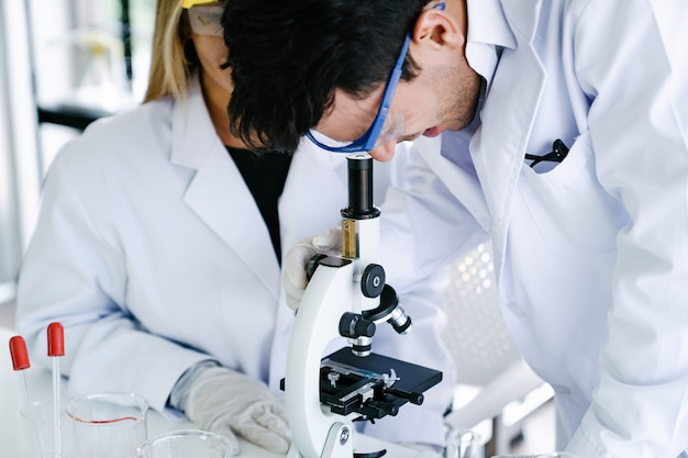 Scientists looking through microscope checking experiment while doing health and medical research