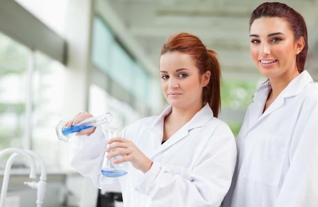 三角フラスコに青い液体を注ぐ科学者