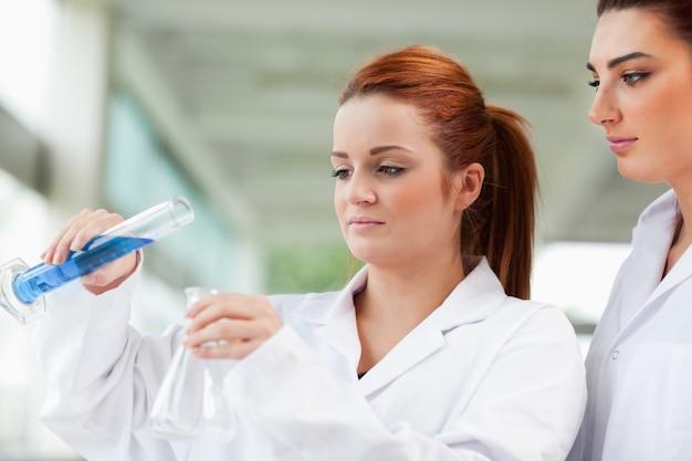 三角フラスコに液体を注ぐ科学者