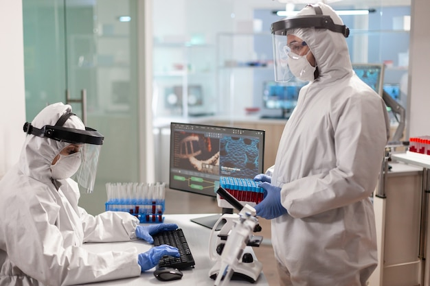 Scientists in protection suits analysing test tubes with blood sample in chemical lab. team doctors working with various bacteria, tissue and blood samples, pharmaceutical research for antibiotics.