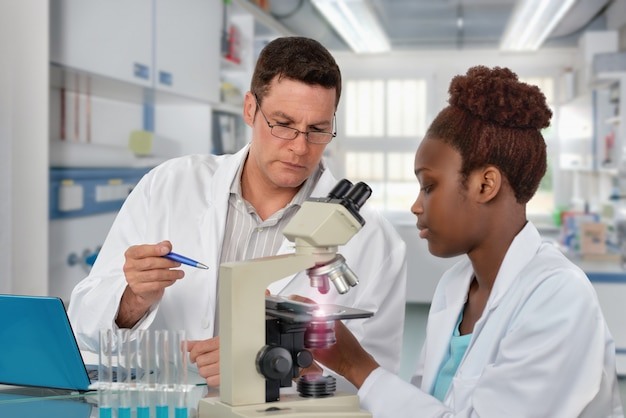 Scientists, senior caucasian male and young african female, work with a microscope in research laboratory