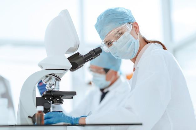Ученые тестируют жидкость и записывают результаты в лабораторный журнал