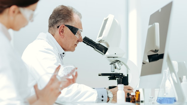Scientists using a microscope to study bacteria in a petri dish.