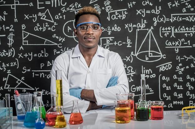 科学者は実験室で眼鏡と腕を組んでいます