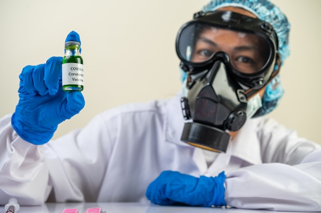 Scientists wearing masks and gloves, carrying vials with vaccines to protect covid-19