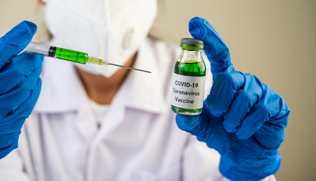 Scientists wearing masks and gloves holding a syringe with a vaccine to prevent covid-19
