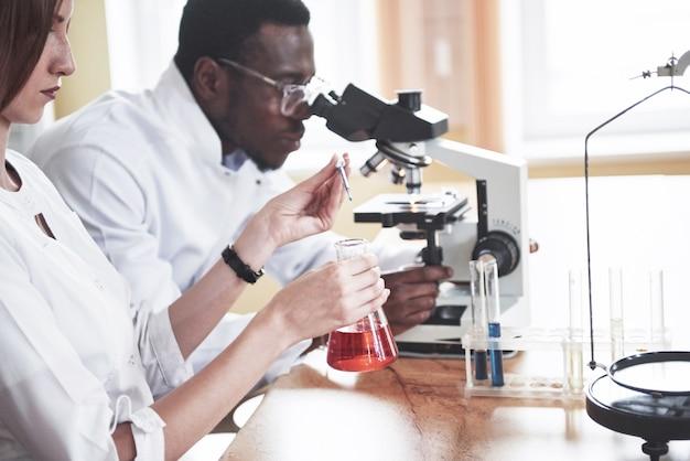 Gli scienziati lavorano a stretto contatto con il microscopio in laboratorio conducendo esperimenti e analisi.