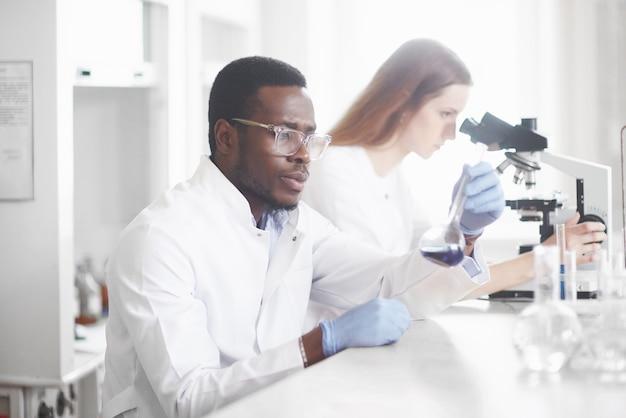科学者は実験と分析を行うことにより、研究室の顕微鏡と緊密に連携します。