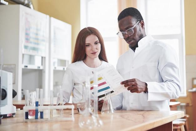 Ученые тесно работают с микроскопом в лаборатории, проводя эксперименты и анализы.