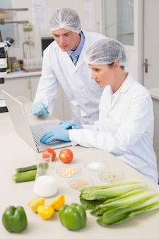 ラップトップと野菜を使って作業する科学者