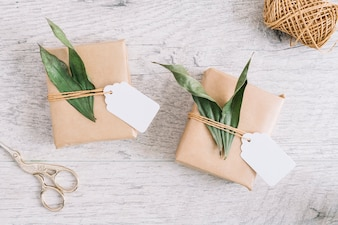 Scissor and wrapped presents with tag and leaves on wooden background