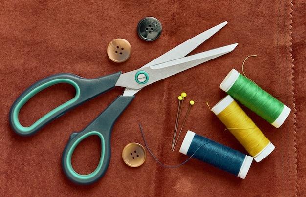 Ножницы, пуговицы, нитки и булавки на замше, вид сверху