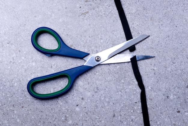 Scissor cutting the black ribbon on the table