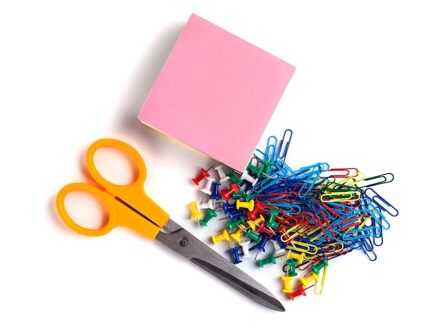 Scissor, tacks, papers and paper clips on white.