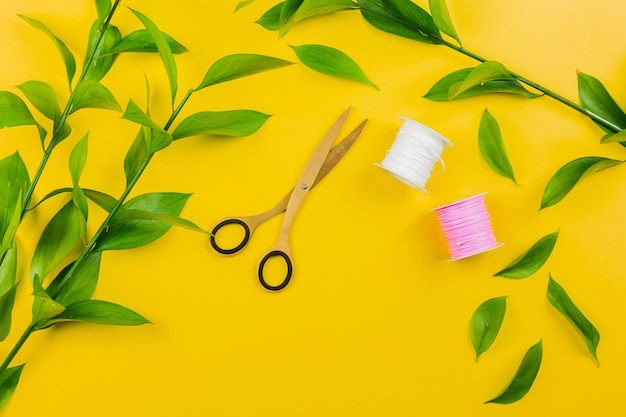 Scissor; thread spools with green leaves twig on yellow backdrop
