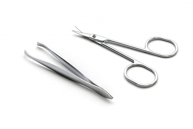 Scissor and tweezers isolated on white surface