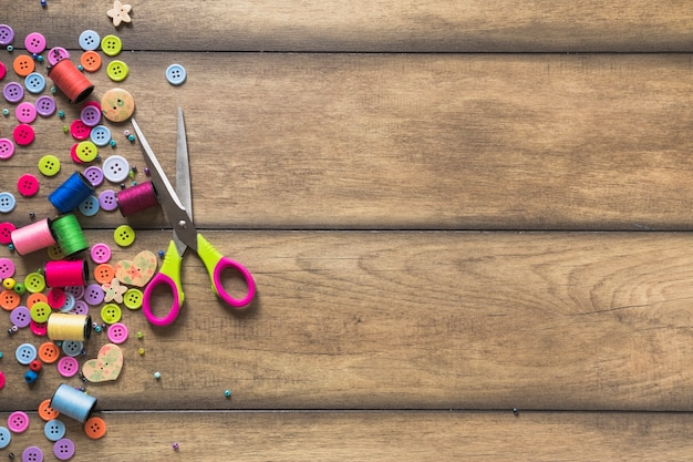 Scissor with colorful spools and buttons on wooden backdrop