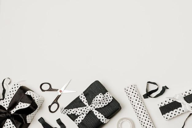Scissor; завернутый подарок и дизайнерская бумага в нижней части фона