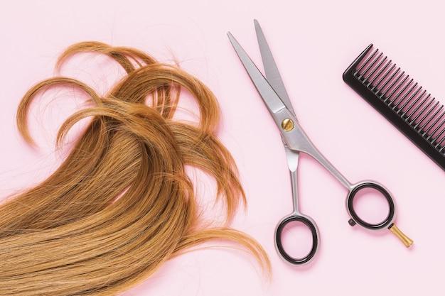 ピンクの表面の上面図に櫛と金髪の女性の子供の髪のカットストランドをはさみ